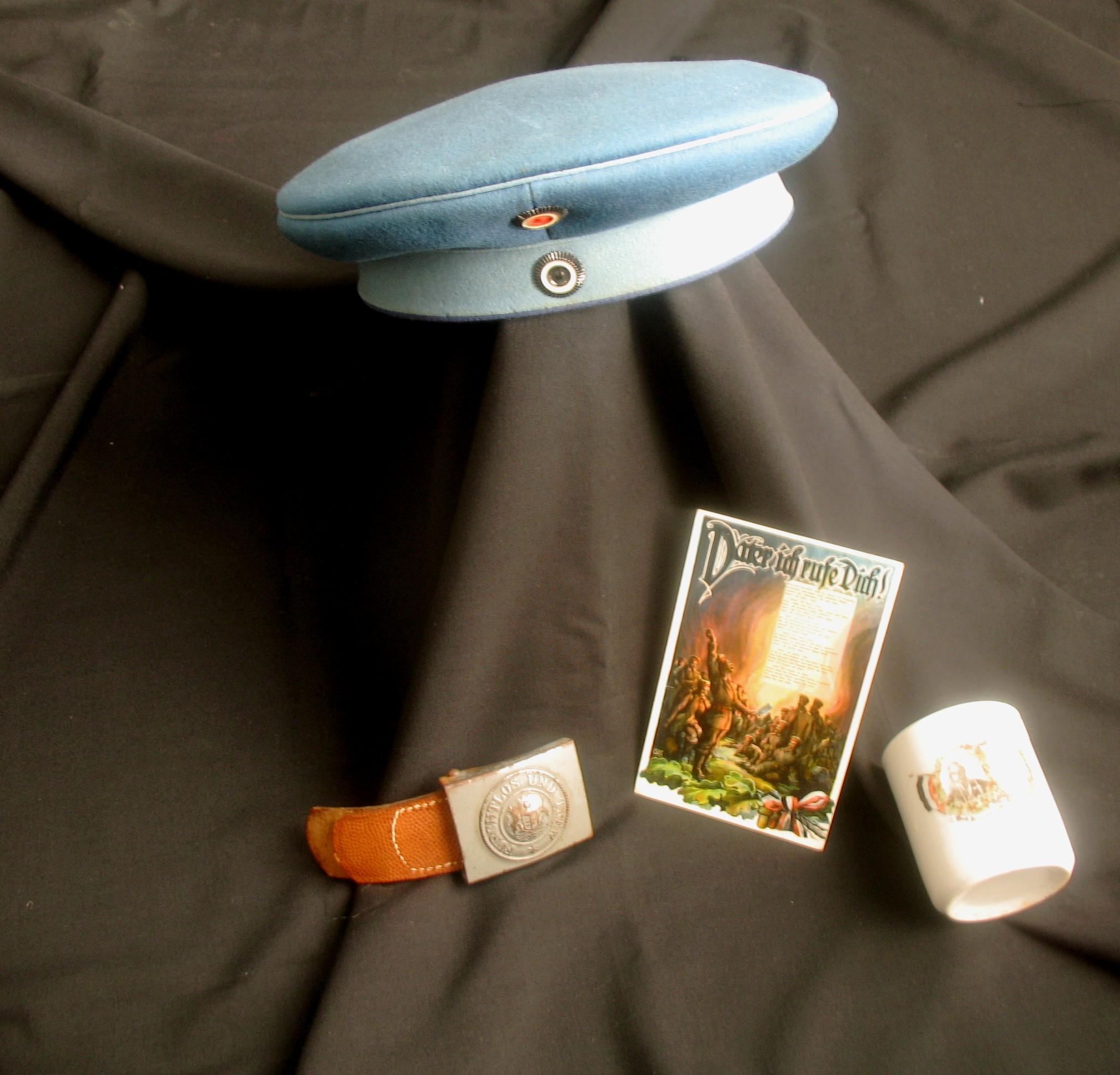 Mütze, boucle de ceinturon, tasse de propagande et carte postale.