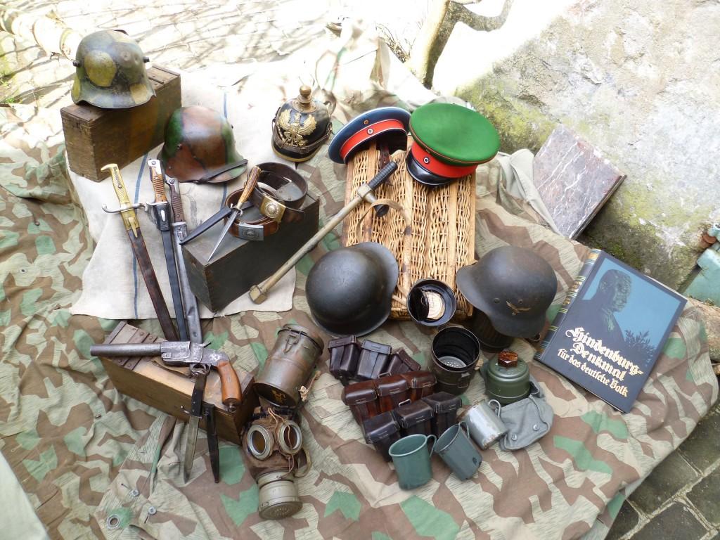 Antiquités militaires proposées à la vente, comprenant des casques allemands dont certains camouflés.